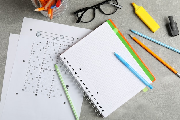 Test sheets, copybook, glasses and stationary on grey surface, top view