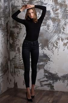魅力的なモデルのテスト撮影は、灰色のスタジオの背景でポーズをとる黒のジーンズと体を着ています