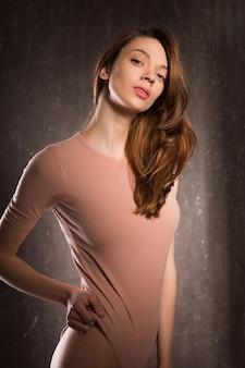 ピンクの下着を着て、影でポーズをとる若い魅惑的な女性のためのテスト撮影