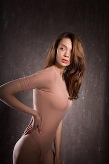 ピンクの下着を着て、影でポーズをとる若い官能的なモデルのテスト撮影
