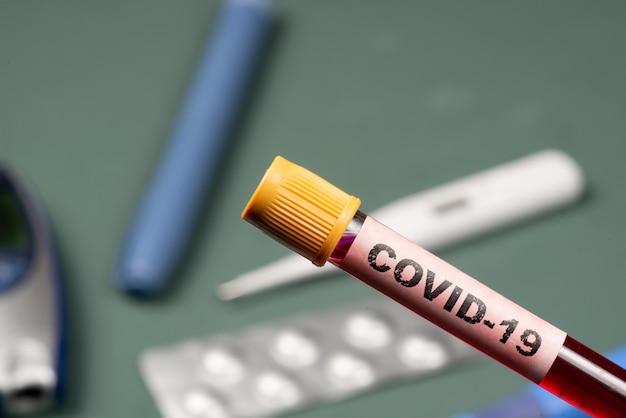 Пробирка с кровью и надписью covid-19 на переднем плане, с размытыми объектами диабета на заднем плане