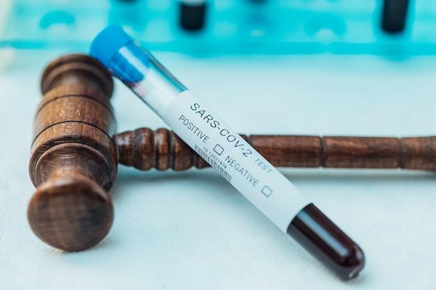 Пробирка с кровью для проведения теста на coivd при поддержке молотка судьи