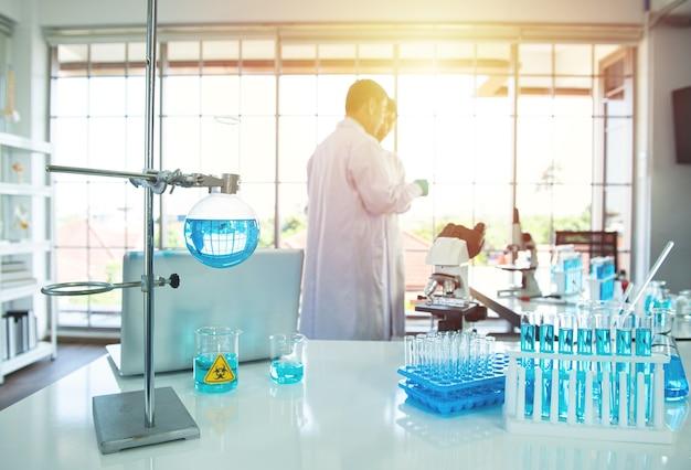 Пробирка с голубой жидкостью в пробирке с учёным на размытом фоне в лаборатории.