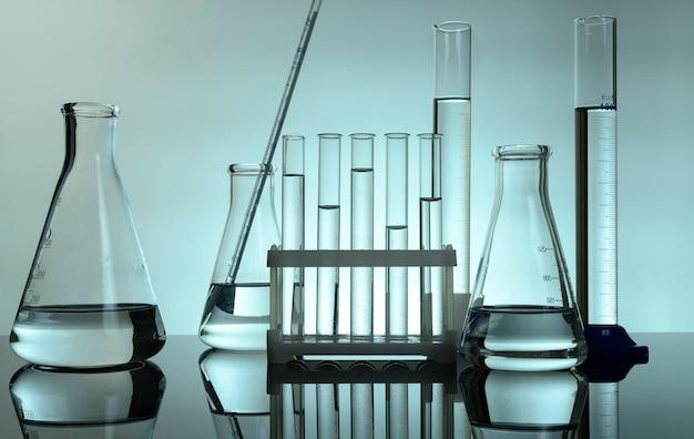시험관과 플라스크는 실험실의 탁자 위에 투명한 액체를 가지고 있다