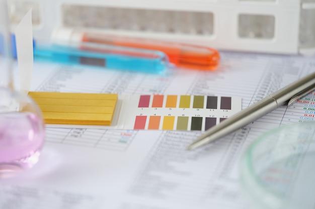 테이블 실험실 연구 홈에 테스트 결과가 있는 파란색 및 주황색 액체가 있는 테스트 튜브