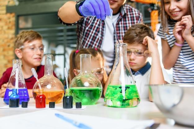 カラフルな液体物質が入った試験管。液体状態の研究。テストチューブを持つグループの学校の生徒は化学液体を研究します。科学のコンセプト。液体の実験を提供する女の子と男の子。