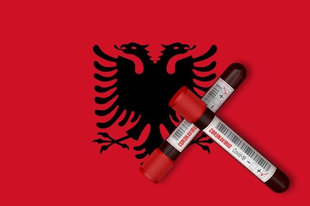 알바니아 국기 배경에 2019-ncov가 새겨진 시험관. 3d 렌더링