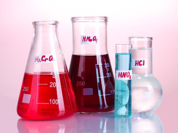 ピンクにさまざまな酸や化学物質が入った試験管