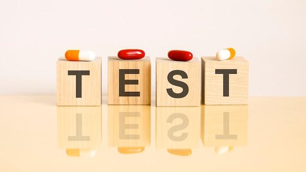 テスト。机の上の木製のブロックの言葉。ピルソンを背景にした医療コンセプト。治療、予防および副作用の医学的概念