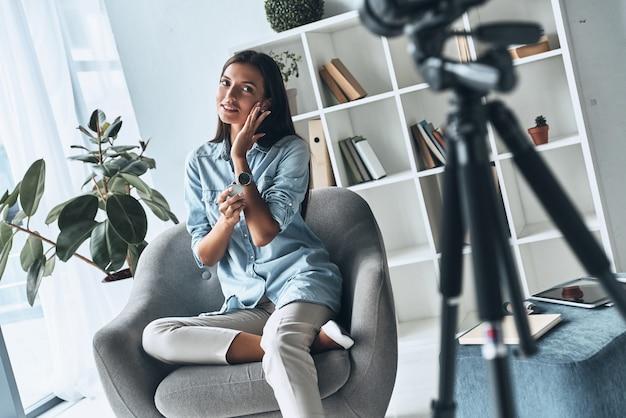 美容製品のテスト。屋内で新しいビデオを作りながら新しい化粧品を適用する魅力的な若い女性