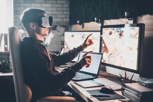 ゲームのテスト。バーチャルリアリティヘッドセットを身に着けて、創造的なオフィスの彼の机に座って身振りで示す若い男