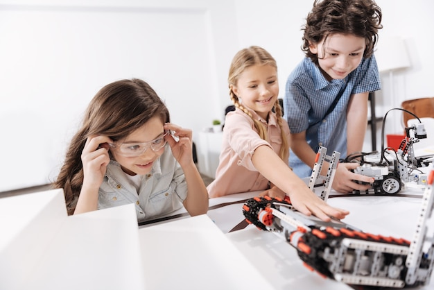 Тестирование современных устройств. вдохновленные, веселые, веселые дети сидят в школе и играют с кибер-роботами во время урока естествознания