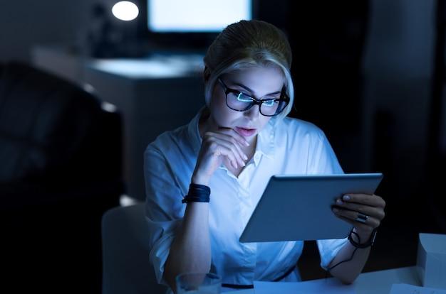 직장에서 새로운 가제트를 테스트합니다. 세심한 젊은 매력적인 it 여성이 사무실에 앉아 태블릿을 사용하면서 프로젝트 작업을하고 관심을 표명합니다.