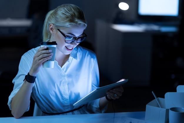 새로운 가제트 테스트. 프로젝트에서 작업하는 동안 사무실에 앉아 태블릿을 사용하는 귀여운 젊은 미소 it 여자