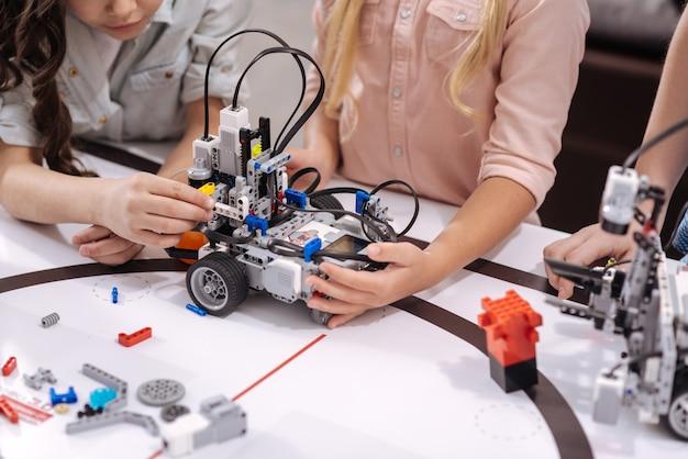 技術発明を一緒にテストします。スマートな自信には、学校に座って科学の授業を受けながらサイバーおもちゃをテストする学童が含まれていました