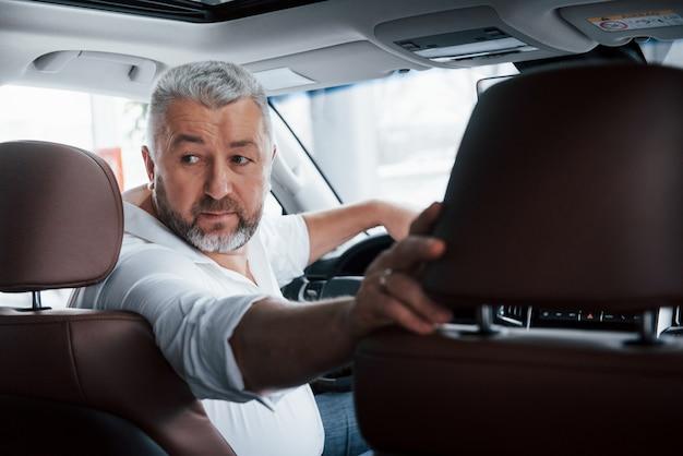 차량 테스트. 후진 기어로 차를 운전. 뒤를 내려다 보면서 그의 새로운 자동차에있는 남자