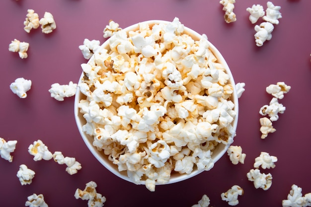 Testy warm popcorn viewed from above on red background