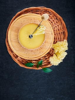 Tete de moine cheese on the device cheese cutter and on a braided basket on a dark background, shallow depth of sharpness