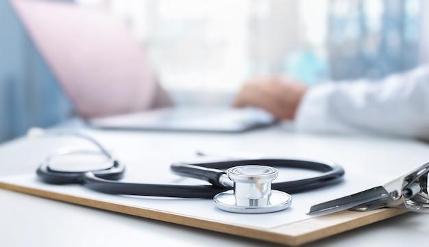 Тетоскоп и клипборд на столе врача крупным планом