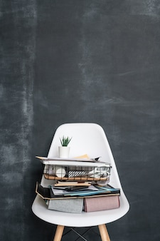 Texile samples, basket with supplies for work of contemporary designer of interior and other stuff on plastic chair against blackboard