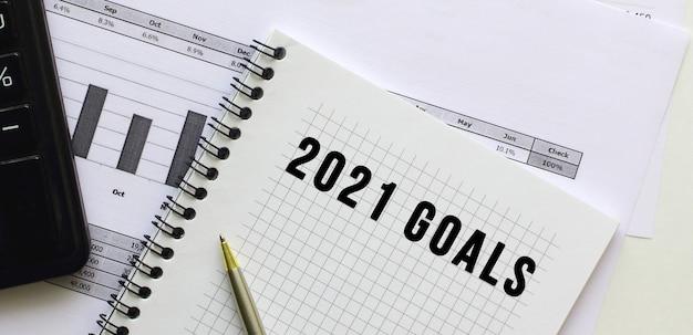 オフィスデスクの財務チャートにあるメモ帳のページに2021goalsとテキストを入力します。電卓の近く。ビジネスコンセプト。