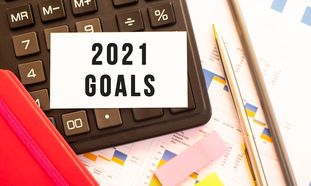 Text 2021 goals on white card with metal pen, calculator and financial charts. business and financial concept