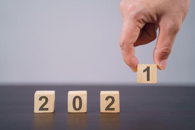 灰色で分離された木製の立方体のテキスト2021。新年のカウントダウンの概念。