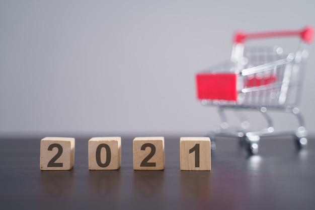 灰色で隔離のショッピングカートと木製の立方体のテキスト2021。新年のカウントダウンの概念。