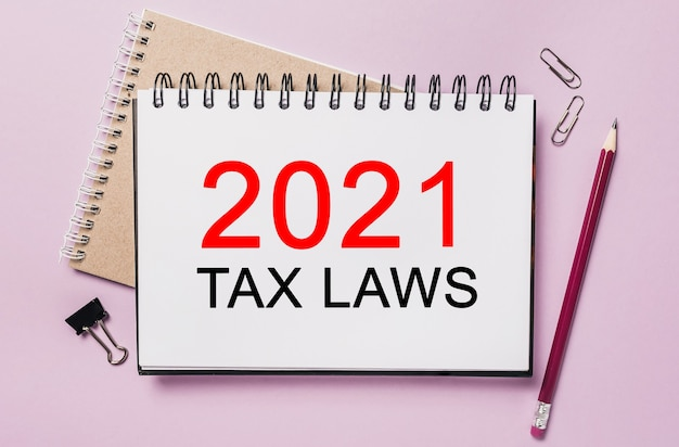 Text 2021 tax laws on a white notepad with office stationery space