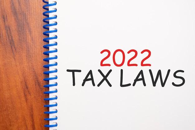 Текст 2022 налоговых законов, написанный в блокноте, офисный деревянный стол сверху, концептуальное изображение для заголовка блога или изображения заголовка. выдержанный винтажный цвет.