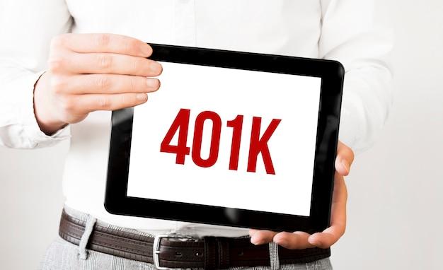 태블릿에 텍스트 401k는 흰색 bakcground에 사업가 손에 표시됩니다. 비즈니스 개념