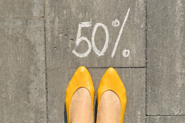 Text 50 percent written on gray pavement with woman legs