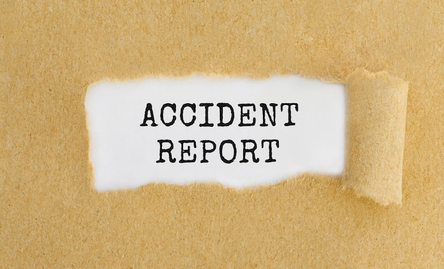 Text accident report appearing behind ripped brown paper