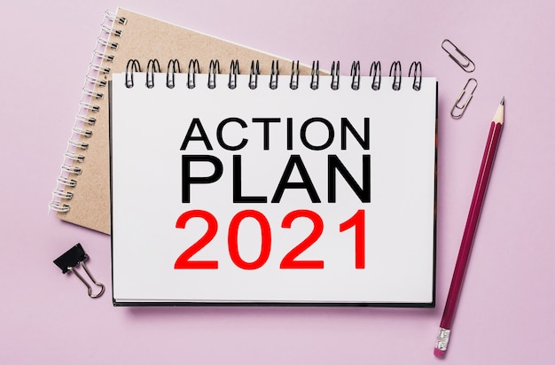 Text action plan 2021 on a white notepad with office stationery background. flat lay on business, finance and development concept