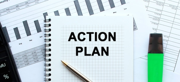 Text action plan on the page of a notepad lying on financial charts on the office desk