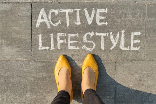 女性の足で灰色の舗装に書かれたテキストアクティブなライフスタイル、上からの眺め