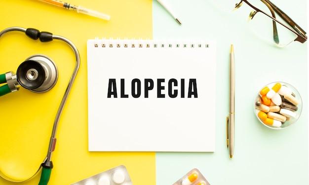 黄色の背景に聴診器とペンでノートにalopeciaとテキストを送信します。