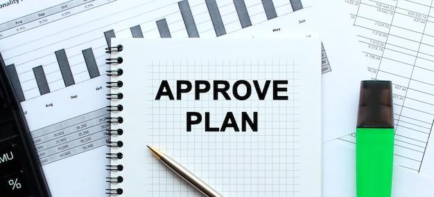 Текст approve plan на странице блокнота, лежащей на финансовых графиках. .