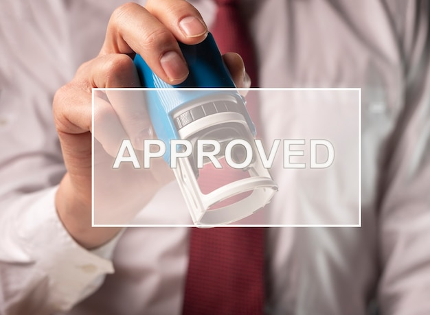 Text approved on photo with hands verifying and stamping document, contract.