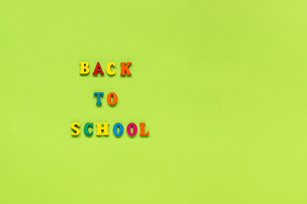 Text back to school from multi colored letters on green paper