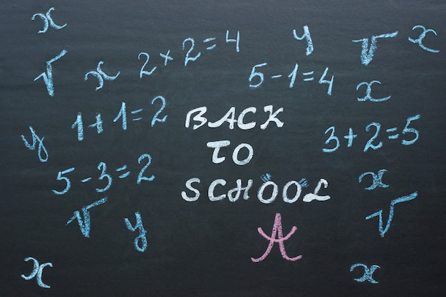 Text back to school and mathematical examples on black chalkboard