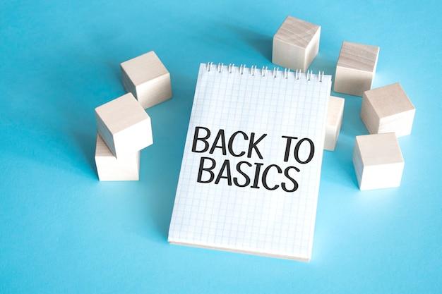 Текст назад к основам на белом блокноте с блоком куба, концепция запаса.