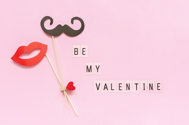 Text be my valentine and couple paper mustache, lips props fastened clothespin heart