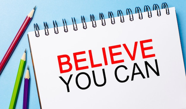 Text believe you can on a white notepad with pencils on a blue background. business concept