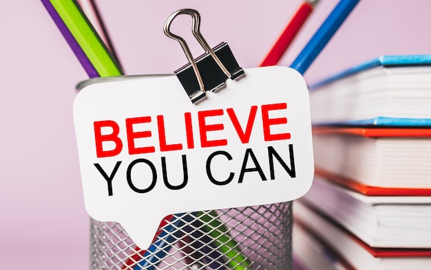 Text believe you can on a white sticker with office stationery background. flat lay on business, finance and development concept