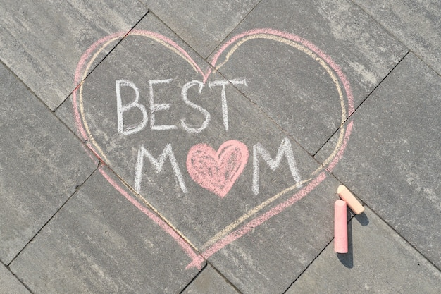 Text best mom written on gray sidewalk in crayons, mothers day