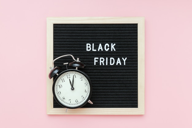 Text black friday on black letter board and alarm clock on pink background. concept black friday , season sales time