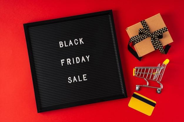 Текст черная пятница на черной доске с буквами подарочная корзина и кредитная карта и на красном фоне