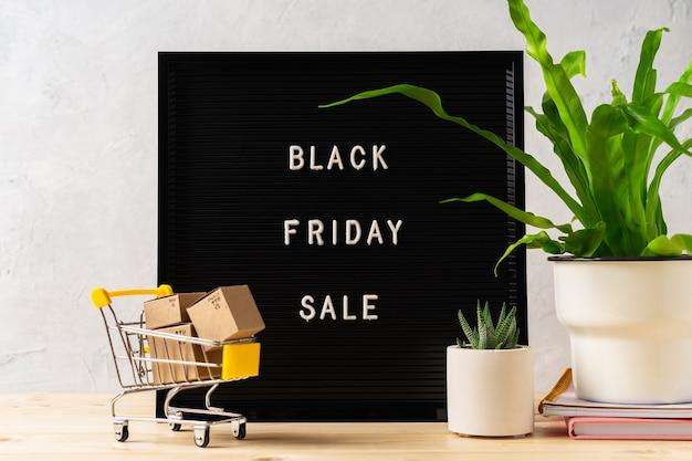 Текст черная пятница на черной доске с буквами растения корзина с коробками на деревянном фоне концепции