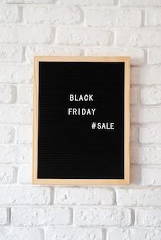 Текст черная пятница распродажа на черной доске для букв на белой кирпичной стене